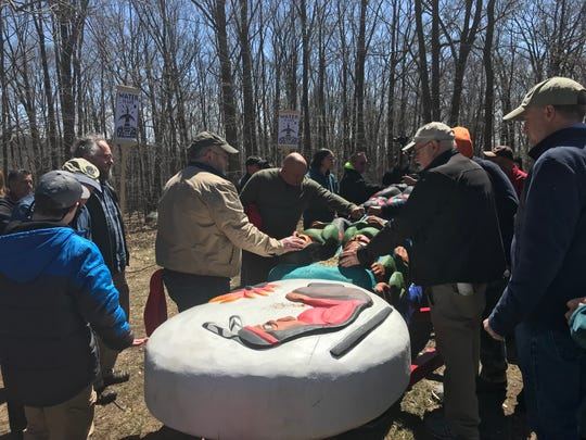 Several people touch a traveling totem pole in Mahwah