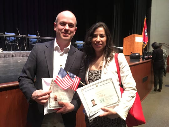 Mauricio Calvo and his wife, Yancy Villa-Calvo, pose with their U.S. citizenship certificates after a swearing-in ceremony April 19 at the University of Memphis Rose Theatre.