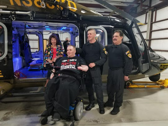 Ryan Stevenson poses for a picture with his grandmother, Ellen Peek, Jonathan King and Rajiv Gupta, two of the people that manned his crew to R Adams Cowley Shock Trauma Center.