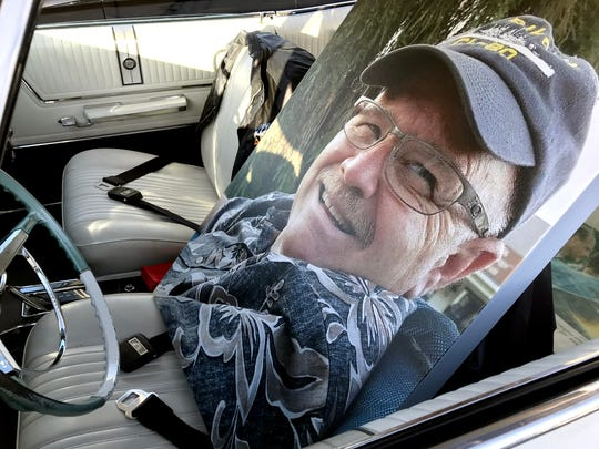 A mounted photo of Doug Carney is propped up in the driver's seat of his car, a white Impala Super Sport, during Saturday's Kool April Nites gathering at Big League Dreams. Carney, who died unexpectantly in August, was board president of the classic car show.
