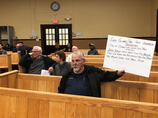 Garfield resident Mike Denistran held a sign against the redevelopment of Columbus Park at the April 3 council meeting.