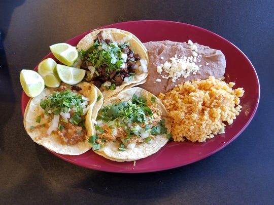 A trio of authentic tacos with beef cheek, tinga (chicken