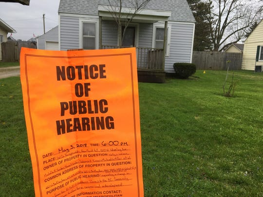 A notice of public hearing on a rezoning petition is posted in front of one of the houses to be razed for redevelopment of an ALDI grocery store and Texas Roadhouse steakhouse in Muncie.