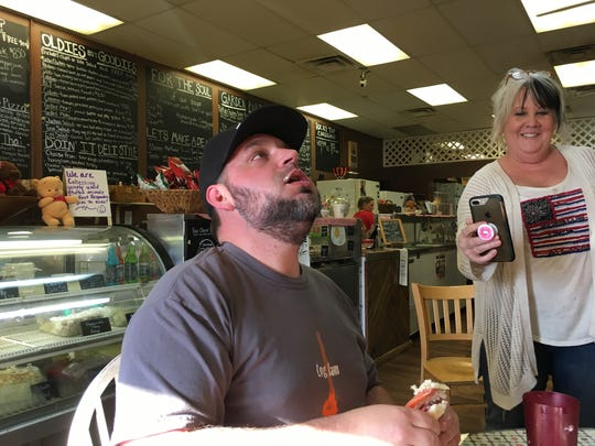 Professional competitive eater Matt Cohen belches during the 4/20 eating challenge at It's All So Yummy Cafe while owner Kim Moegenburg Wilcox captures it on Facebook Live.