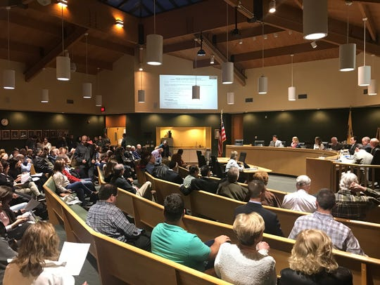 An overflow crowd packs the council chambers to discuss