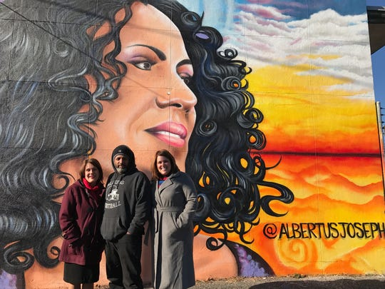 """The Gateway Neighborhood welcomes visitors to the City of Perth Amboy with a mural called """"Hometown Girl"""" by resident Albertus Joseph, pictured in the center with . Mayor Wilda Diaz, left, and Lisett Lebron, project manager of Perth Amboy Redevelopment Team for Neighborhood Enterprise and Revitalization (P.A.R.T.N.E.R.). The Gateway is one of the city's four federally mandate Opportunity Zones that aim to bolster development and job creation."""