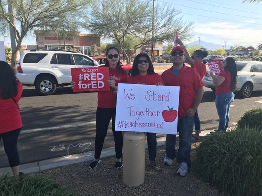 Jessica Lozano (from left), Martha Avendano and Manny Avendano rally for #RedForEd along Baseline Road on April 25, 2018.