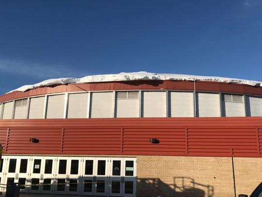 Snow from a blizzard that dropped 2 feet of snow hangs from the roof of the Brown County Veterans Memorial Arena. Falling snow crushed the roof of the building below.