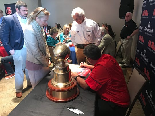 Matt Luke signs autographs for Ole Miss fans at the Rebel Road Trip's stop in Birmingham.