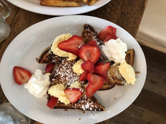 French toast with powdered sugar, whip cream, strawberries
