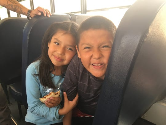 Ava Cook, 7, eats a peanut butter and jelly sandwich on a school bus with her silly 8-year-old brother, Anthony.