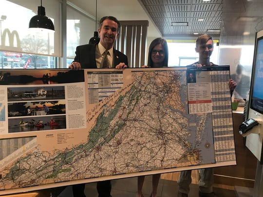 Gov. Ralph Northam, McDonald's Owner and Operator Tiffany Beach and Onley resident William Ennis display a map of Virginia inside the in Onley McDonald's Wednesday evening.