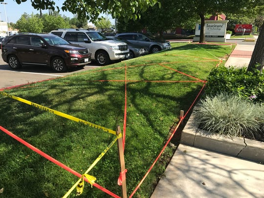Tape covers a stretch of grass outside a business on Hilltop Drive Thursday. Officials say businesses want to make sure they can use their land to see Friday's Kool April Nites parade.