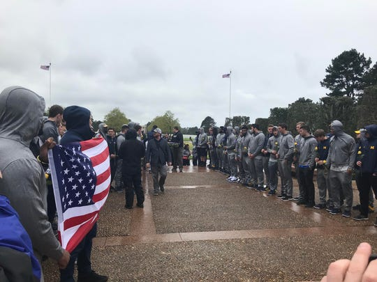 Michigan players and coaches participate in a ceremony at the Normandy American Cemetery on Sunday, April 29, 2018.