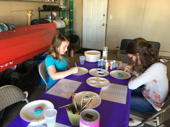 Olivia Nahan, 10, and Jenalyn Ostendorf, 15, paint their own kindness rocks at Kylie's Kickin' Cancer Lemonade Stand.