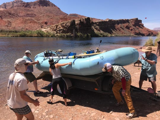 Members of Russ Peterson's rafting group lift one of their nine rafts into the Colorado River at Lees Ferry. They'll spend much of the day prepping and packing before they launch the next morning.