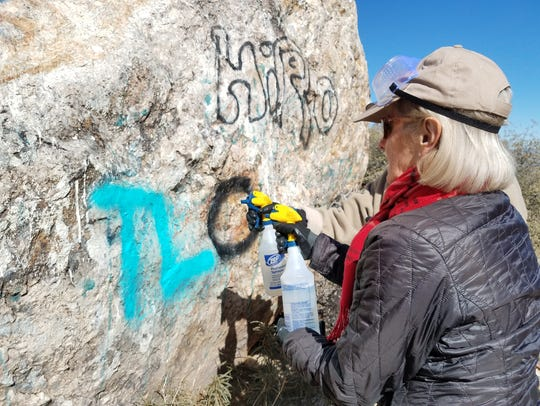 A volunteer removes graffiti at the Gold Butte National