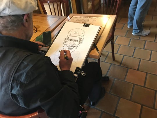 A sketch artist draws Michigan coach Jim Harbaugh on
