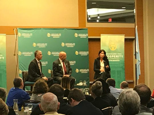 Kristi Noem, right, speaks at a candidate forum in Sioux Falls Tuesday night. Marty Jackley, left, and Americans for Prosperity State Director Don Haggar, center, listen.