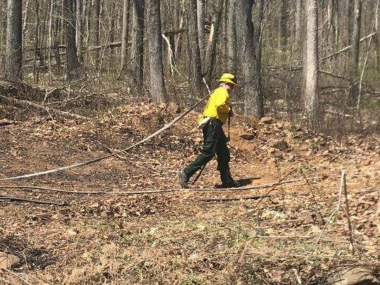 A firefighter collects a hose at the scene of a brush