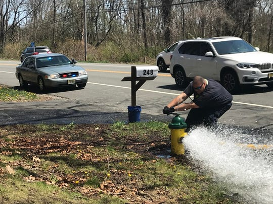 A firefighter battles a hydrant on Route 206 during