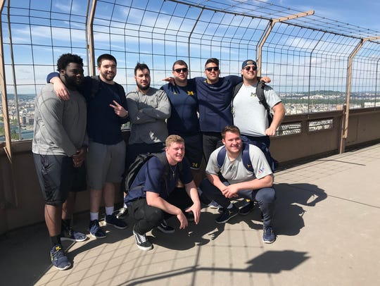 Members of Michigan's offensive line pose on the Eiffel
