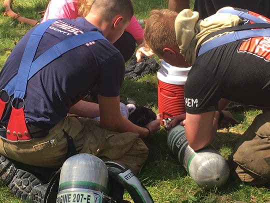 Firefighters are shown giving oxygen to a rescued puppy.