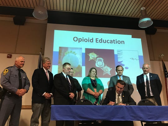 Gov. Ralph Northam signs Senate Bill 399 during an opioid awareness program at Eastern Shore Community College in Melfa, Virginia in May 2018. The landmark legislation aims to give Virginia cities and counties another tool to fight future deaths caused by the opioid epidemic.