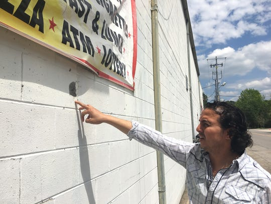 Owner Hany Geriss points to bullet holes in the wall