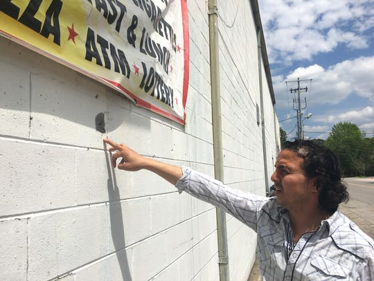 Owner Hany Geriss points to bullet holes in the wall outside JD's Market after a drive-by shooting Wednesday after shots were fired in the intersection of East Vine and South Maney in Murfreesboro.