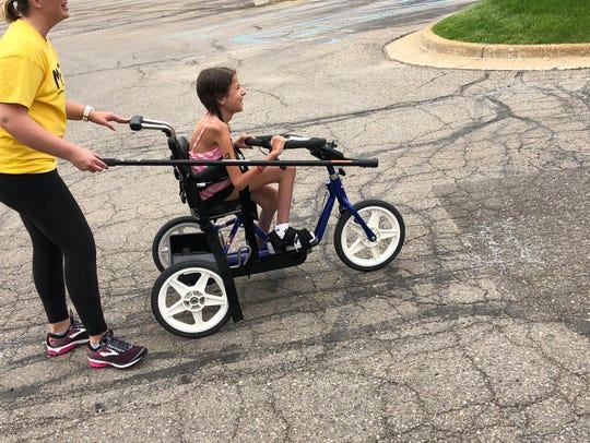 Ellie Kerrigan, 12, of Belleville, participates in the University of Michigan Mott Children's Hospital adaptive triathlon at Domino's Farms in Ann Arbor Sunday.