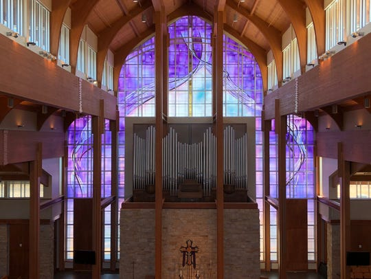 The stained-glass window at Holy Family was installed in three phases.