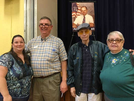Alvin Randlett's friends Cheryl and Jeff Siska of Florence and Richard and Bonnie Klette of Covington gather inside the Sixth District Elementary School gym in front of a photograph of Randlett. Randlett, a janitor at the school, willed $175,000 to child abuse victims.