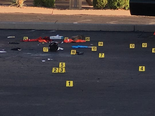 Investigators marked evidence in a Mesa parking lot where ICE agents shot a suspect May 8, 2018.