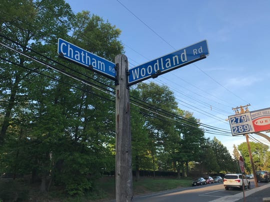 A sign at the intersection of Chatham Road and Woodland