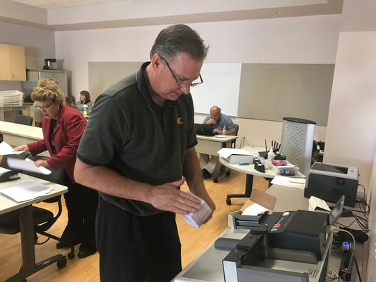 Election worker Dan Pabich from Martin & Chapman inserts