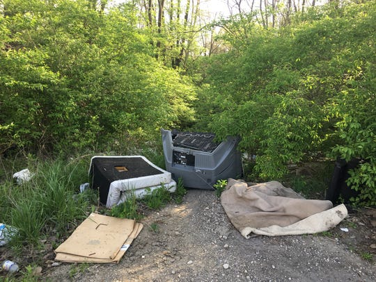 Trash is dumped at the head of a trail leading to White