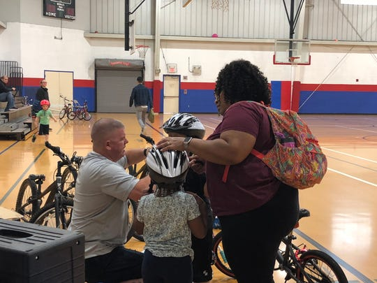 Charlotte Gunter, 4, and Noah Gunter, 6, get fitted for their helmets before learning to ride a bike at the Wilmington Police Athletic League Saturday.