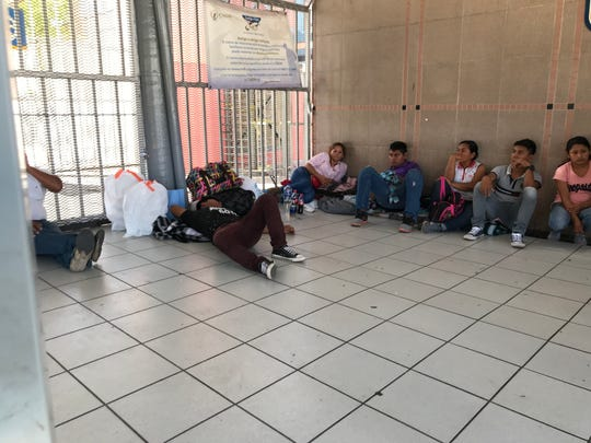 Guatemalan migrants take a break from standing outside