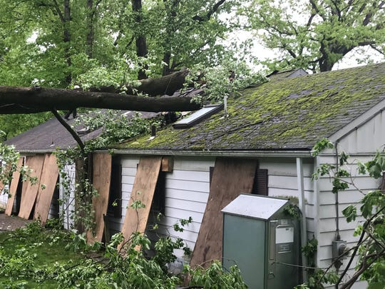 Workers remove a tree that crashed into this house