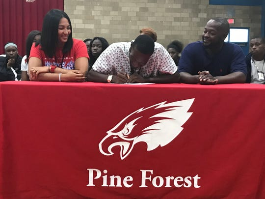 Pine Forest senior Lucas Davis (center) signs with