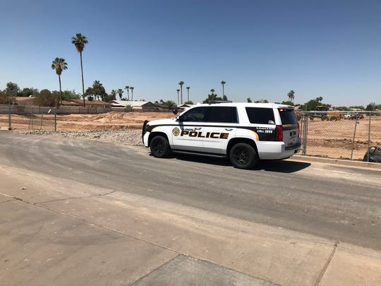 A Glendale police squad car is parked on North 71st Avenue near where police say two kidnapped men escaped captivity.