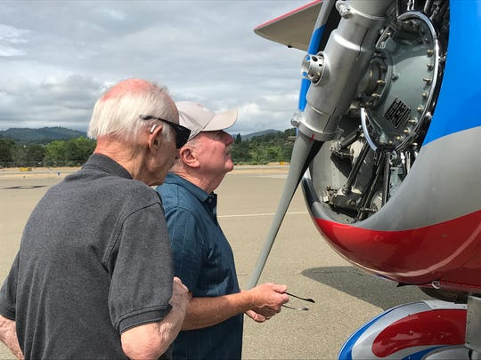 Redding resident Ken Cook, wearing cap, gets a close look at one of the three biplanes.