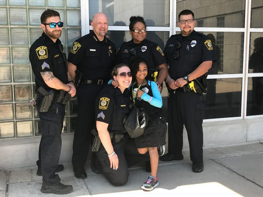 Rosalyn Baldwin, 8, poses for a photo with officers from the University of Wisconsin-Milwaukee Police Department, including Chief Joe LeMire (second from left).