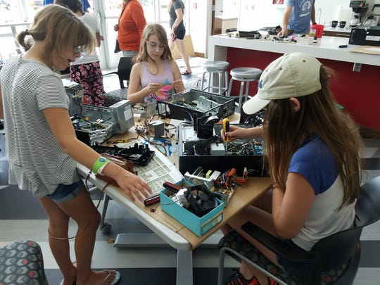 Girls take apart electronics at the first Girls Breaker Day in 2017.