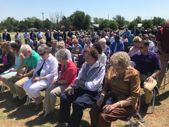 Attendees of the Hardin-Simmons University groundbreaking for the Houston-Lantrip Center for Literacy and Learning bow their heads in prayer Thursday.