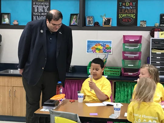 State Rep. Andre Jacque watches as a first-grader at Koenig Elementary in Two Rivers shows him how to measure a plant May 18.