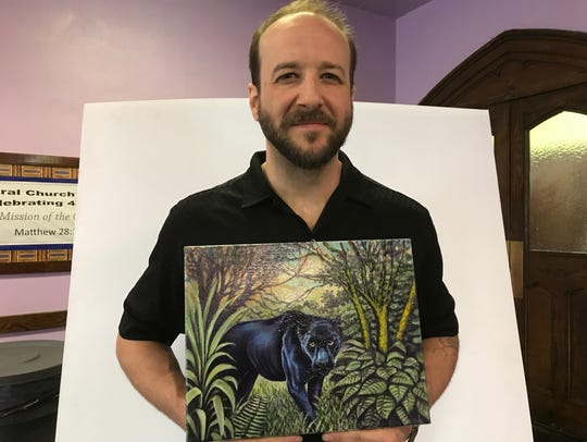 Michael DeLuca holding the winning panel painting.