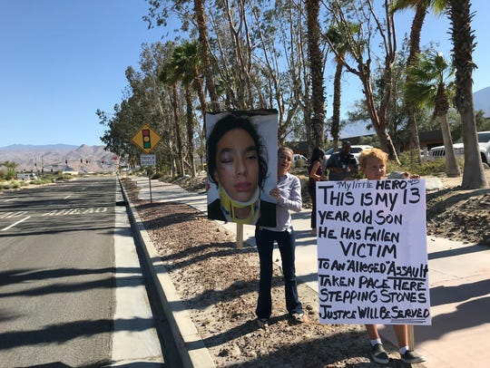 Storey Lantry Chavira stands with a sign in front of