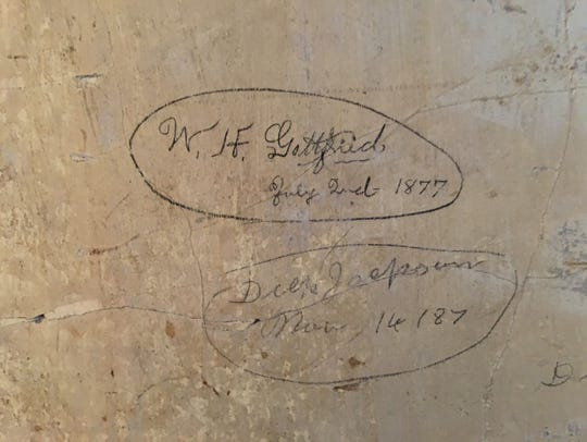 Under the wallpaper and the plaster is the signature of William H. Gottfried, a builder and businessman who died in 1930.